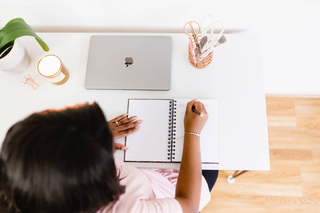 Woman writing in a planner at a desk