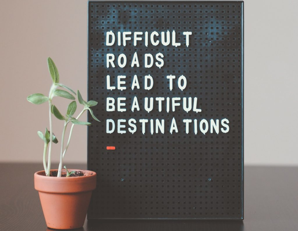 """Difficult roads lead to beautiful destinations"" quote on board"
